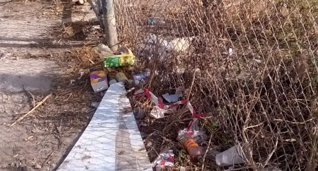 Plastic waste next to a fence